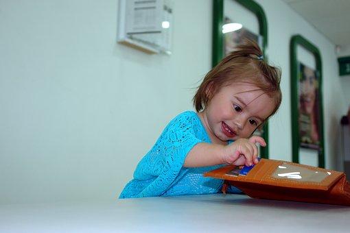 Une fille qui joue avec le porteefeuille de papa